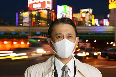 Portrait confident businessman in face mask in city at night, Tokyo, Japan