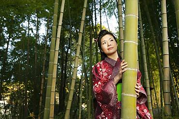Portrait beautiful curious young woman in Japanese kimono among bamboo trees