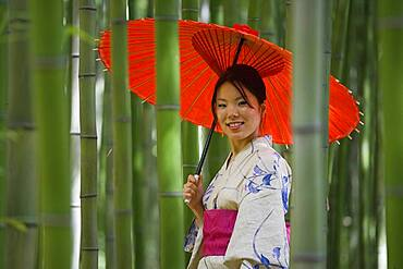 Portrait beautiful young woman in kimono with parasol among bamboo