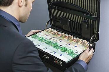 Businessman looking at briefcase full of cash Euros