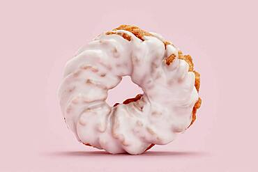 Close up frosted pink cruller donut