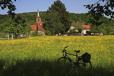 Bicycle parked in sunny idyllic meadow behind church, Tauber valley, Germany