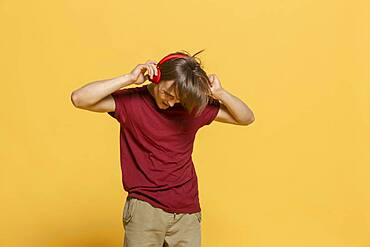 Carefree young man with headphones listening to music