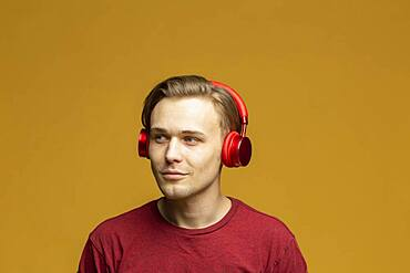 Studio portrait young man with headphones listening to music