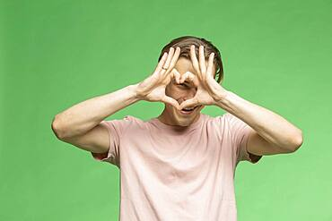 Portrait young man gesturing heart shape with hands