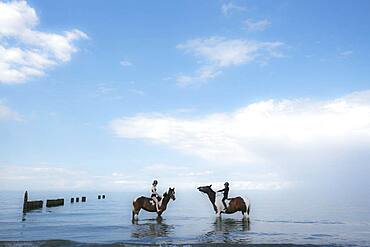 Girls riding horses in Baltic Sea, Germany