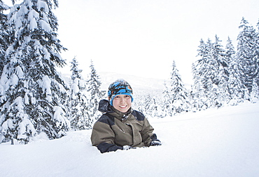 Portrait of smiling boy buried in snow
