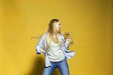 Carefree young woman dancing against yellow background