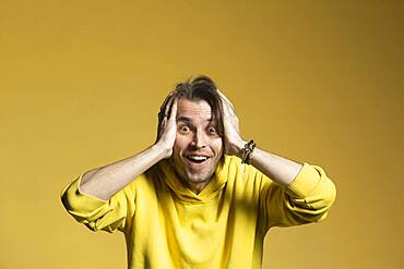 Portrait excited, surprised man on yellow background