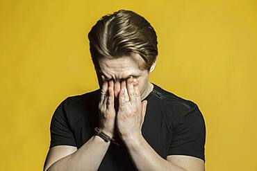 Tired, stressed young man rubbing eyes on yellow background