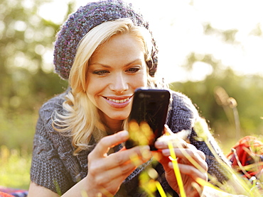 A smiling woman looking at her smart phone