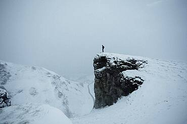 Hiker on remote snow covered cliff, Peak District National Park, England