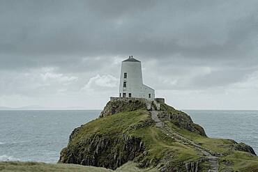 Lighthouse on ocean cliff under cloudy sky, Angelsey, Wales