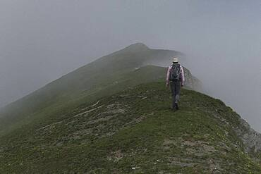 Man with backpack hiking on mystical, foggy mountain, Piedmont, Italy