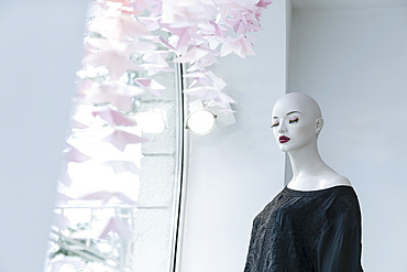 Mannequin with eyes closed in boutique window