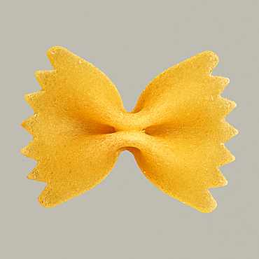 Close up uncooked farfalle bowtie pasta on gray background
