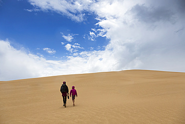 Mother and son walking along remote sand dunes, Wilsons Promontory, Victoria, Australia