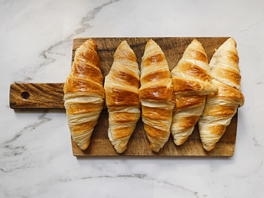 View from above fresh croissants on wooden cutting board