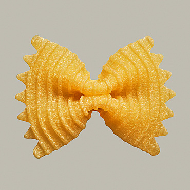 Close up uncooked farfalle bow tie pasta noodle on gray background
