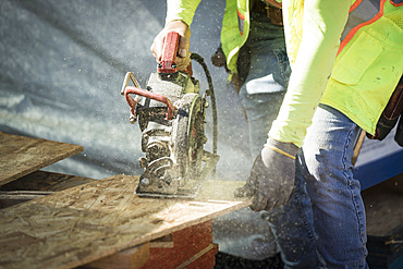 Construction worker using saw on plywood