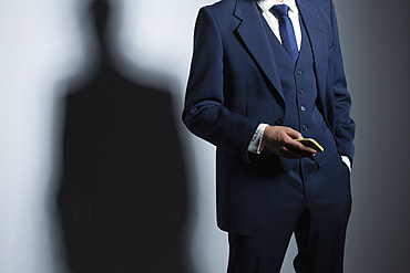 Businessman in suit holding smart phone