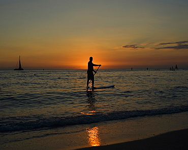 Silhouetted man on stand up paddle board during sunset