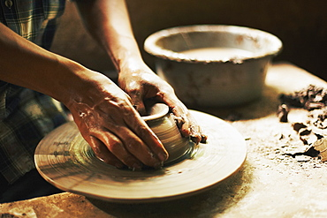 Cropped image of potter moulding clay in workshop
