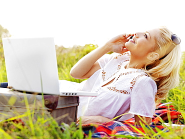 A woman in nature with an open laptop and using a mobile phone