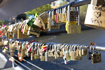 Large group of love padlocks on railing against lake