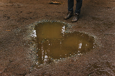 Low section of person standing by heart shaped puddle