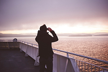 Rear view of man photographing sea on pier at nanaimo ferry terminal