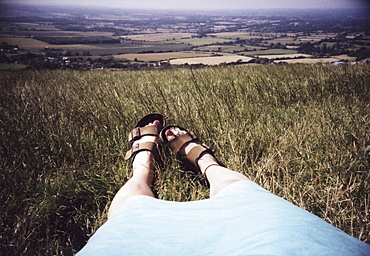 a woman's legs and feet outstretched in grass overlooking fields