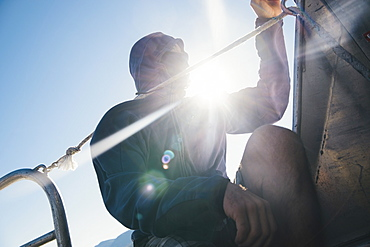 Low angle of man sitting on boat against clear sky