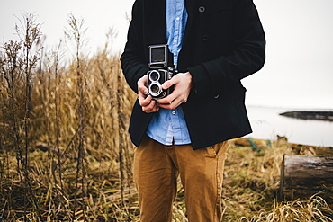 Midsection of man photographing through retro styled camera in park
