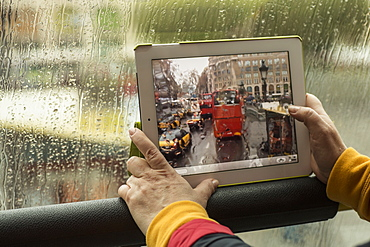 Cropped image of woman photographing bus with digital tablet