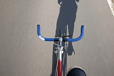 Person riding bicycle with shadow falling on street