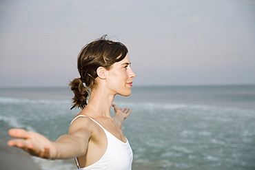 Woman standing on beach with arms outstretched