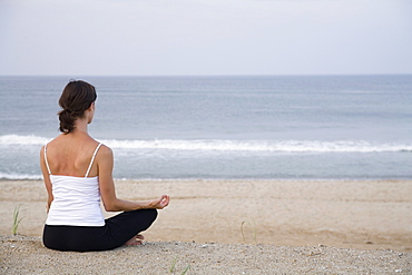 Woman sitting on beach in lotus position