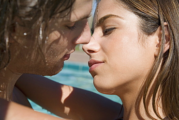 Young couple about to kiss by swimming pool