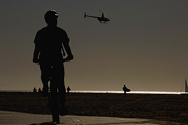 A helicopter flying above a beach at sunset