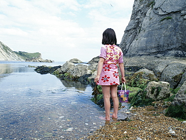 A young girl paddling in shallow water