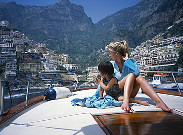 A mother and son on a boat on the amalfi coast