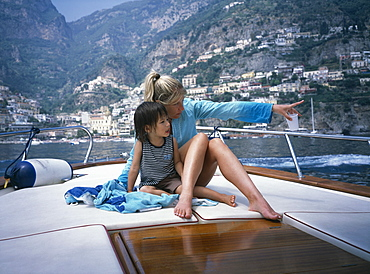 A mother and son sitting on a boat on the amalfi coast