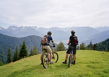 Two cyclists on the top of a hill looking at the view