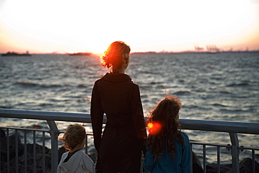 A mother and two children looking out to sea