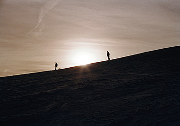 Two skiers on a mountain side at sunset