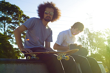 Two skateboarders sitting in a skate park