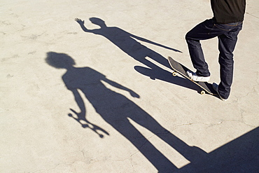 Shadows on two skateboarders on concrete