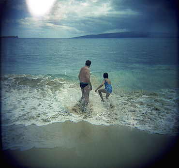A man and woman splashing in the waves