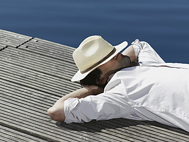 A young man lying on a jetty